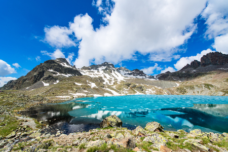 Small colored alpine lake with last ice in the summer Stock Photo