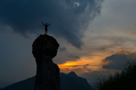 conquers: Man conquers the top of a mountain after a hard climb