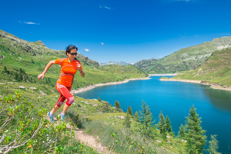 Woman in technical clothing runs in mountain path above a beautiful alpine lake Stock Photo