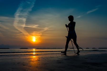 Woman practicing Nordic walking by the sea in a dawn late summer Stock Photo