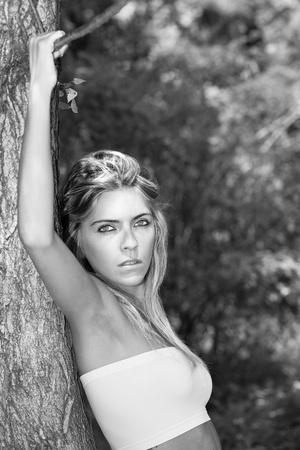 Portrait in black and white style movie star Beautiful blonde woman with intense eyes leaning against a tree with hands on branch