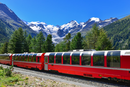 Swiss mountain train Bernina Express crossed Alps with glaciers in the backgroundin the summer