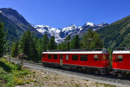 locomotora: tren de montaña suizo Bernina Express cruzó los Alpes con los glaciares en el backgroundin el verano