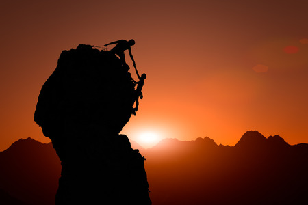 roped: Team of climbers help to conquer the summit in teamwork during a climb roped in a fantastic mountain landscape at sunset