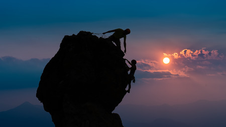 roped: Team of two mountaineers roped help you with your hand to win the top Stock Photo