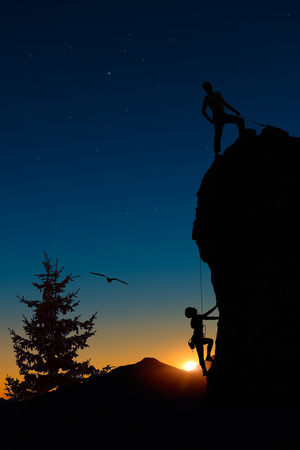 roped: Team of two mountaineers roped climb the mountain. The first at the top makes safety and helps the second.