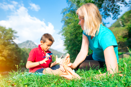 Naturopath practicing reflexology at the foot of a child in nature