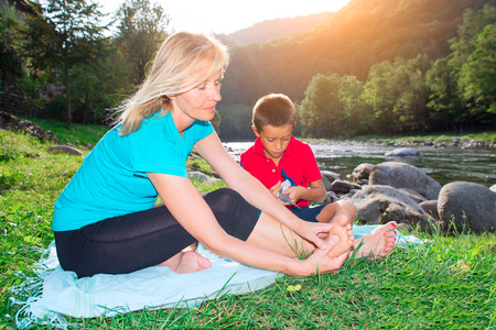 Naturopath practicing reflexology at the foot of a child near a river Stock Photo