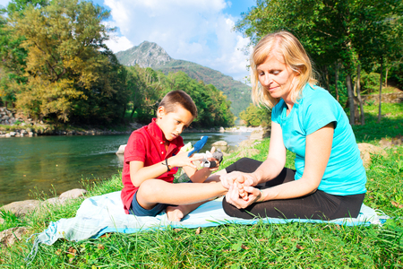 naturopath: Naturopath practicing reflexology at the foot of a child near a river Stock Photo