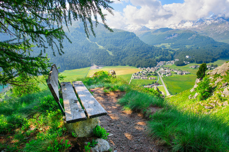 Wooden bench overlooking mountain landscape in the summer