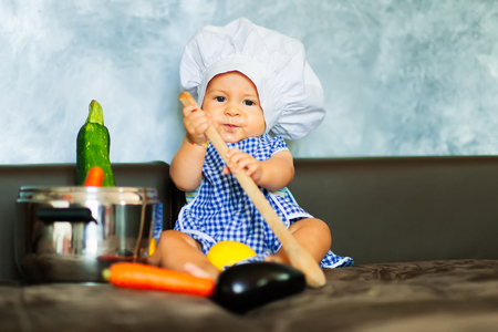 Little boy playing at being a chef at home