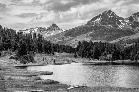 swiss alps: Alpine scenery with lake in the mountains of the Swiss Alps in black and white fine-art Stock Photo