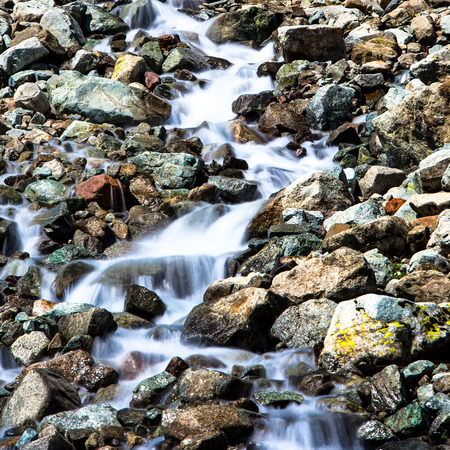 Waterfall between the rocks of the mountains in the Alps Stock Photo