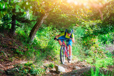 A young male riding a mountain bike outdoor He lowers his head under the plants