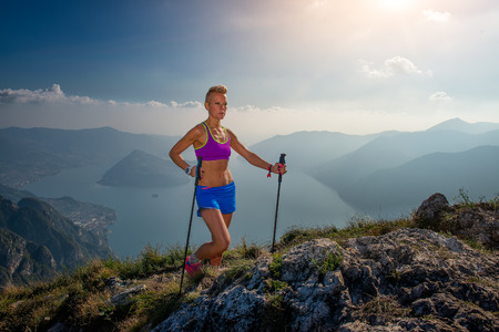 Trail running in the mountains athlete girl with sticks Stock Photo