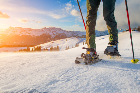 snowshoes: Detail of man walking with technical snowshoes in mountains Stock Photo