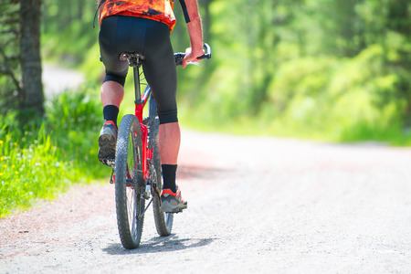 road bike: Mountain bike rider in the gravel road in summer