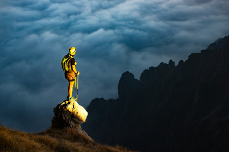 Fantastic sunset in mountains with hiker on a stone where he arrived last ray of sunshine. Observes the valley surrounded by a sea of clouds Stock Photo