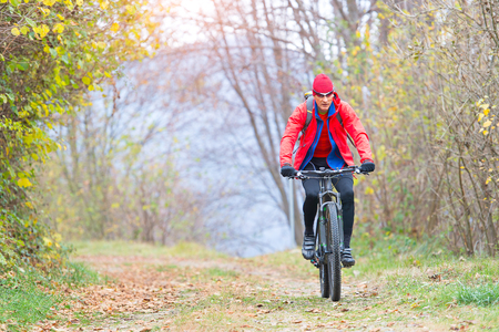 Sporty man relaxes pedaling a mountain bike in the woods in autumn