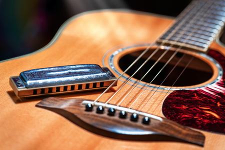 Akoestische gitaar met country blues harmonica klaar op het podium
