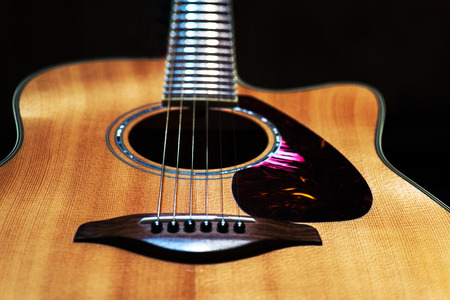 Cuntry-style acoustic guitar in black background