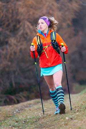 Young sporty blonde girl active practice Nordic walking in a mountain meadow