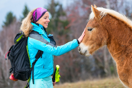 Girl during a trek in the mountains caresses horse