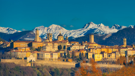 The city of Bergamo with high behind the White Mountains of snow the early morning sun Banque d'images