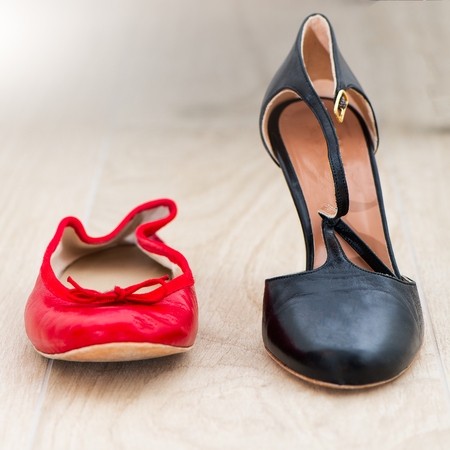 Red Shoes ballet flats and nearby black heels on withe background Stock Photo