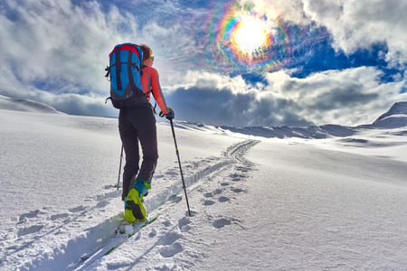 Girl makes ski mountaineering alone toward the mountain pass in a nice track with sealskin