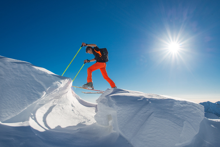 A man alpine skier climb on skis and sealskins  in so much snow with obstacles in una giornata di sole forte