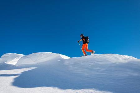 A man alpine skier climb on skis and sealskins In alpine ridge of alps