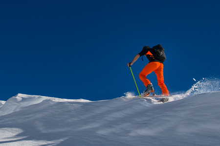 A man alpine skier climb on skis and sealskins in fresh snow
