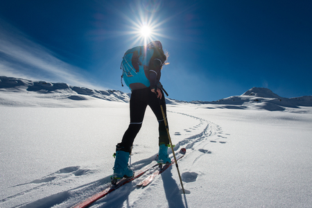 Ascent with ski mountaineering and climbing skins for a single woman in snow landscape