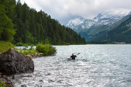 Canoeist alone in the lake of the Alps Stock Photo