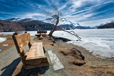 Wooden bench to admire the scenery on an alpine lake ice near Sankt Moritz in Switzerland