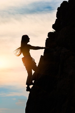 Girl alone during a climb in a fantastic mountain landscape at sunset in summer Stock Photo