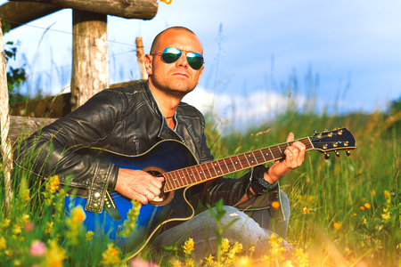 Singer with guitar plays alone in a meadow in nature-