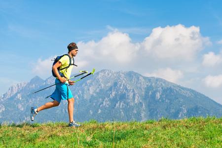 Jonge mens die fysieke activiteitenberg uitoefent en met stokken loopt. Stockfoto