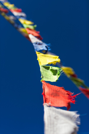 Closeup of colorful Tibetan Buddhist prayer flags waving in the wind on blue sky background.