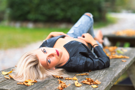 Sexy blonde naked girl laying on a wooden bench in autumn.