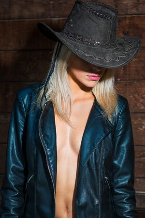 Sexy country girl wearing cowboy hat and leather jacket  - portrait in a barn.