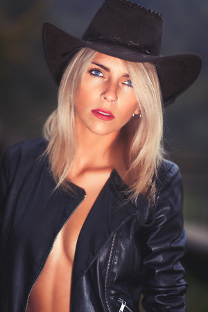 Sexy country girl wearing cowboy hat and leather jacket  - portrait in a barn. Stock Photo - 88281849
