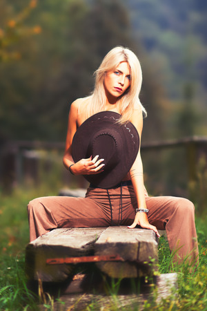 Sexy naked country girl covering her breast with a cowboy hat and sitting on a wooden bench  - portrait outdoor with a fence on the background.