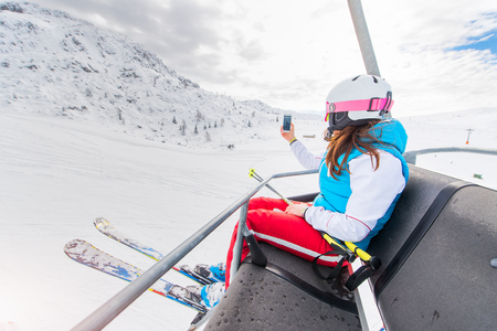 Girl skier in ski resortchairlift gets a selfie