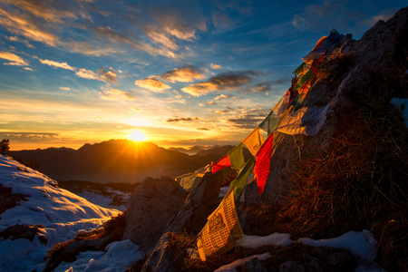 Flags of Tibetan prayers in the mountains with the colors of a warm sunset. Stock Photo