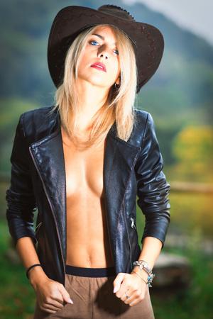 カウボーイ ハットと革のジャケットを身に着けているセクシーな田舎娘。