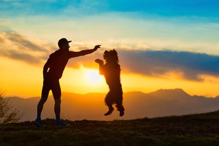 Big dog saltando para tirar um biscoito de uma silhueta de homem com fundo em montanhas coloridas do por do sol.