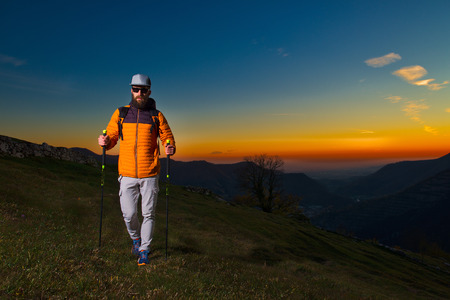 Young man with beard practicing nordic walking in a colorful sunset. Stock Photo