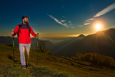 Young man with beard watching the panorama is resting during a nordc walking trek. Foto de archivo